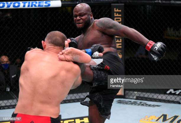 In this handout photo provided by UFC, Derrick Lewis kicks Aleksei Oleinik of Russia in their heavyweight fight during the UFC Fight Night event at...