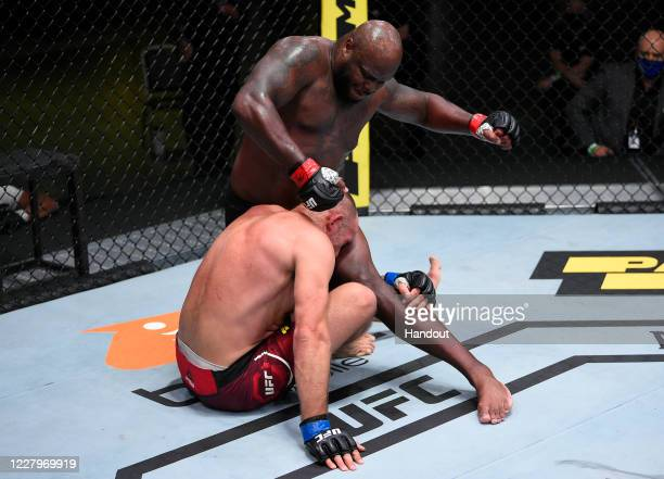 In this handout photo provided by UFC, Derrick Lewis punches Aleksei Oleinik of Russia in their heavyweight fight during the UFC Fight Night event at...