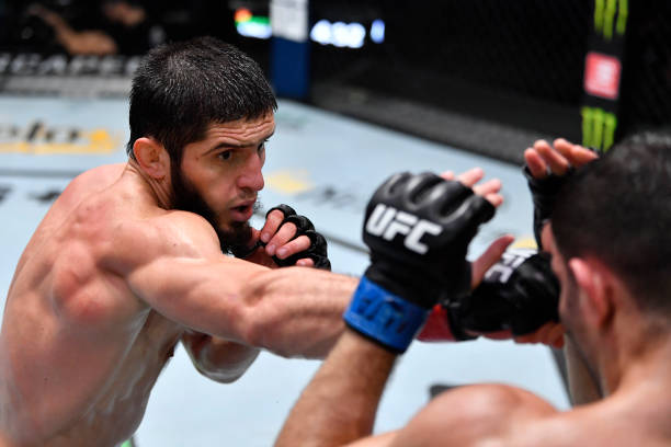 In this handout photo provided by UFC, Islam Makhachev of Russia punches Thiago Moises of Brazil in their lightweight bout during the UFC Fight Night...