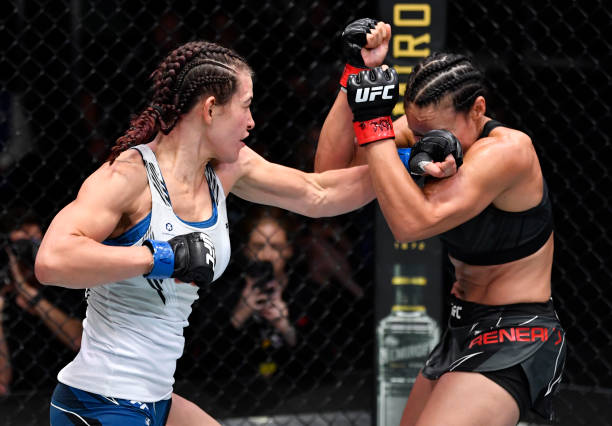 In this handout photo provided by UFC, Miesha Tate punches Marion Reneau in their bantamweight bout during the UFC Fight Night event at UFC APEX on...
