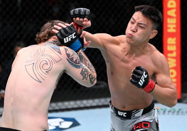 In this handout photo provided by UFC, Rong Zhu of Tibet punches Brandon Jenkins in a lightweight fight during the UFC Fight Night event at UFC APEX...