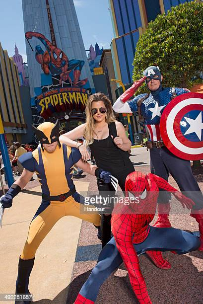 In this handout photo provided by Universal Orlando Resort TV personality Khloe Kardashian poses with SpiderMan Wolverine and Captain America at...