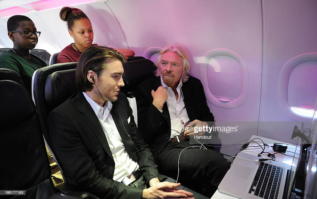 In this handout photo provided by Virgin America Airlines and transmitted at 35,000 feet, Virgin Group Founder Sir Richard Branson (R) celebrates the launch of its new service to Newark, New Jersey from San Francisco and Los Angeles with Mashable CEO & Founder Pete Cashmore onboard aircraft at Newark Liberty International Airport (EWR), April 9, 2013 at Newark, New Jersey. Branson and Cashmore also joined local flyers for a pre-flight Google+ 'Fly Like a Boss' hangout to discuss how technology is changing business and travel.