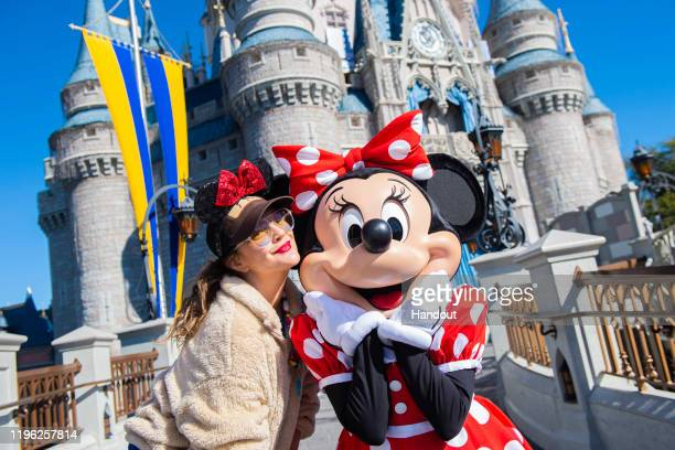 In this handout photo provided by Walt Disney Resorts, actress Drew Barrymore strikes a pose with Minnie Mouse while vacationing with family at Magic...