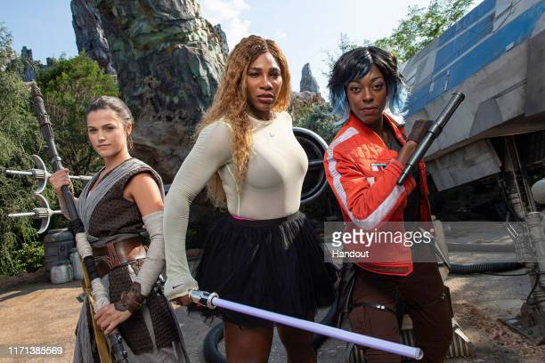 In this handout photo provided by Walt Disney Resorts Serena Williams poses with Rey and Vi Moradi during a visit to Star Wars Galaxys Edge at Walt...