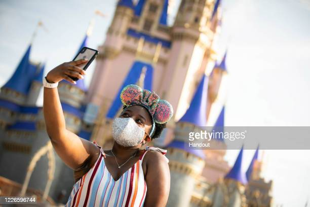 In this handout photo provided by Walt Disney World Resort, a guest stops to take a selfie at Magic Kingdom Park at Walt Disney World Resort on July...