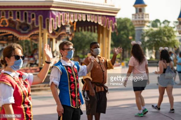 In this handout photo provided by Walt Disney World Resort, Disney cast members welcome guests to Magic Kingdom Park at Walt Disney World Resort on...