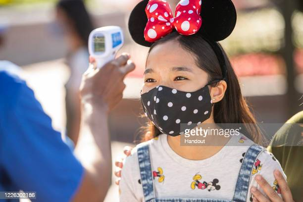 In this handout photo provided by Walt Disney World Resort guests undergo temperature screenings prior to entering a theme park at Walt Disney World...