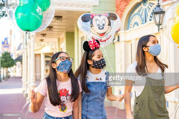 In this handout photo provided by Walt Disney World Resort, guests wear masks at Walt Disney World Resort on June 12, 2020 in Lake Buena Vista,...