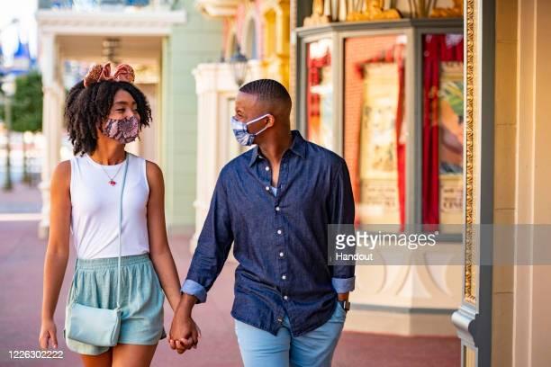 In this handout photo provided by Walt Disney World Resort, guests wear masks at Walt Disney World Resort on June 12, 2020 in Lake Buena Vista,...