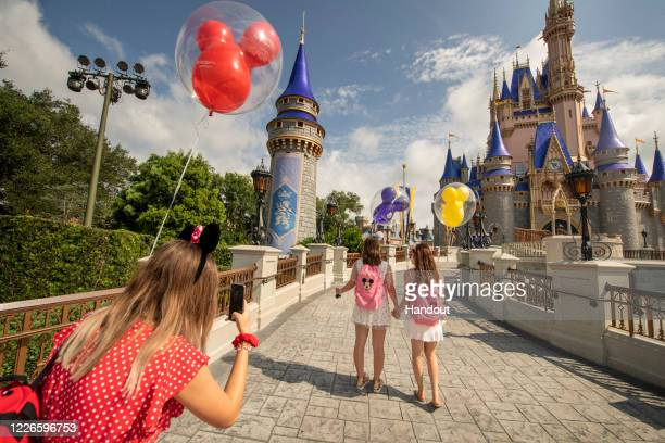 In this handout photo provided by Walt Disney World Resort, Guests stop to take a photo at Magic Kingdom Park at Walt Disney World Resort on July 11,...