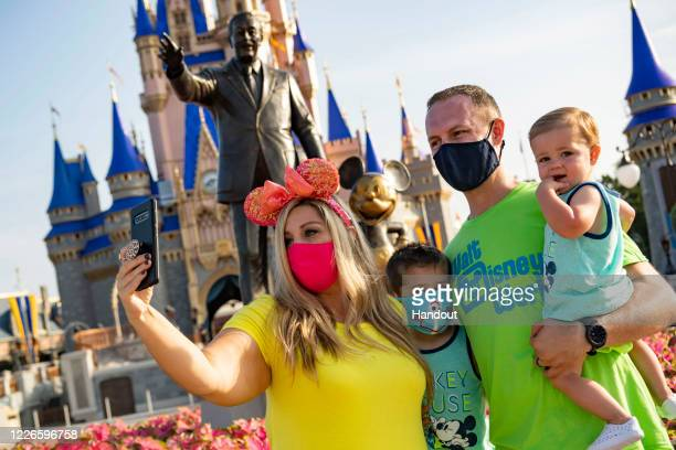 In this handout photo provided by Walt Disney World Resort, guests stop to take a selfie at Magic Kingdom Park at Walt Disney World Resort on July...