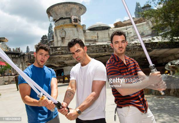 In this handout photo provided by Walt Disney World Resort Nick Jonas Joe Jonas and Kevin Jonas of the Jonas Brothers visitStar WarsGalaxy's Edge...