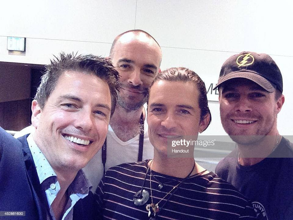 In this handout photo provided by Warner Bros, 'Arrow' star Stephen Amell (far right) and fellow cinematic archer Orlando Bloom (second from right, 'The Lord Of The Rings'/'The Hobbit') pose for a group selfie with 'Arrow's Paul Blackthorne (second from left), taken by Arrow's John Barrowman (who plays Malcolm Merlyn on the show) with Amell's borrowed mobile phone at the Warner Bros. booth during Comic-Con International 2014 on July 26, 2014 in San Diego, California.