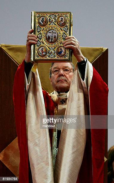 In this handout photo provided by World Youth Day His Eminence Cardinal George Pell Catholic Archbishop of Sydney holds aloft the Holy Bible at the...