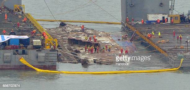 In this handout photo released by Hankook Daily a submersible vessel attempts to salvage sunken Sewol ferry in waters off Jindo on March 22 2017 in...