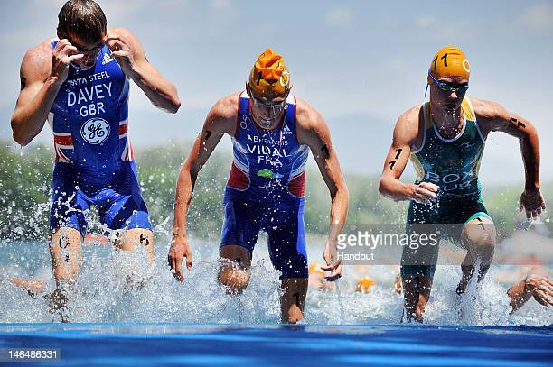 In this handout photo released by the International Triathlon Union, Great Britain's Rhys Davey, France's Laurent Vidal and Australia's Drew Box exit...