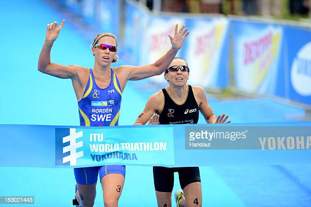 In this handout photo released by the International Triathlon Union Sweden's Lisa Norden barely edges out Germany's Anne Haug at the finish line to...