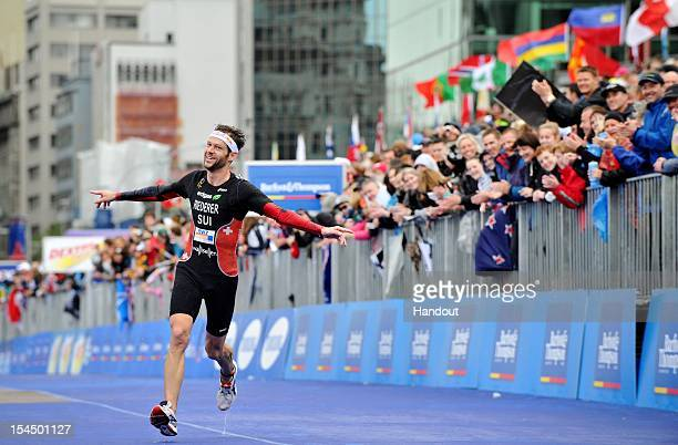 In this handout photo released by the International Triathlon Union Sven Riederer of Switzerland celebrates finishing in 3rd place and winning a...