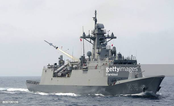 In this handout photo released by the South Korean Defense Ministry a South Korean navy ship fires a missile during a drill aimed to counter North...