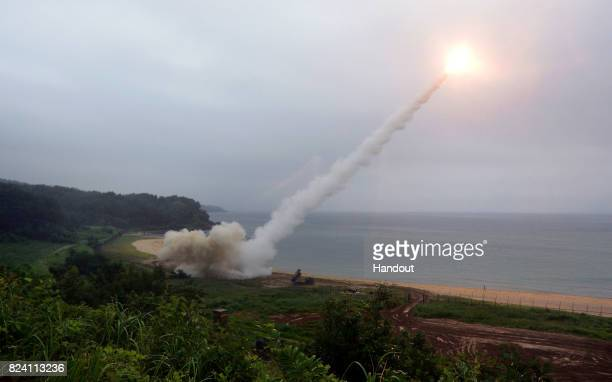 In this handout photo released by the South Korean Defense Ministry US Army Tactical Missile System firing a missile into the East Sea during a South...