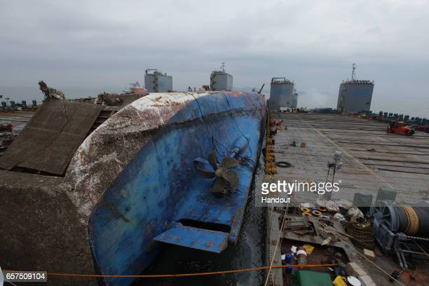 In this handout photo released by the South Korean Maritime Ministry Workers participate in the salvage operation of the Sewol ferry in waters off...