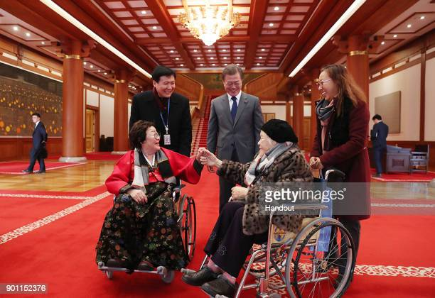 In this handout photo released by the South Korean Presidential Blue House, South Korean President Moon Jae-in meets 'comfort women', former South...