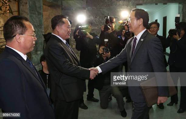 In this handout photo South Korean Unification Minister Cho MyoungGyon shakes hands with North Korean delegation head Ri SonGwon before their meeting...