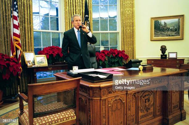 In this handout photo US President George W Bush speaks to Canadian Prime Minister Paul Martin on the phone in the Oval Office in Iraq December 15...