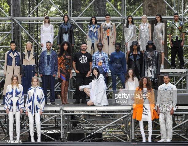 In this handout photograph provided by Burberry, Chief Creative Officer Riccardo Tisci poses with models backstage during the Burberry Spring/Summer...