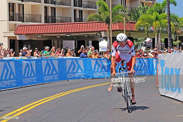 In this handout photograph provided by Ironman Jan Frodeno of Germany finishes first in the 112mile bicycle ride during the IRONMAN World...