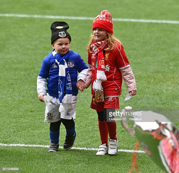 In this handout photograph provided by Liverpool FC a young Liverpool fan holds hands with a young Everton fan as they pay their respects during the...