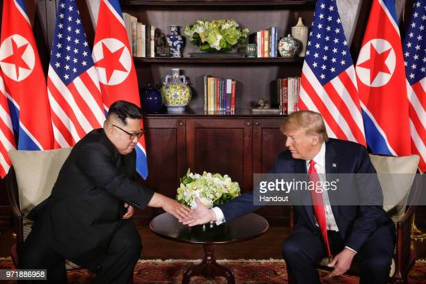 In this handout photograph provided by The Strait Times North Korean leader Kim Jongun shakes hands with US President Donald Trump during their...
