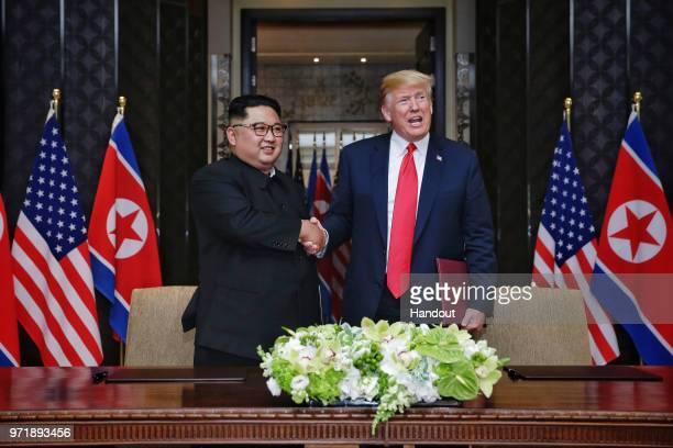 In this handout photograph provided by The Strait Times North Korean leader Kim Jongun with US President Donald Trump during their historic USDPRK...