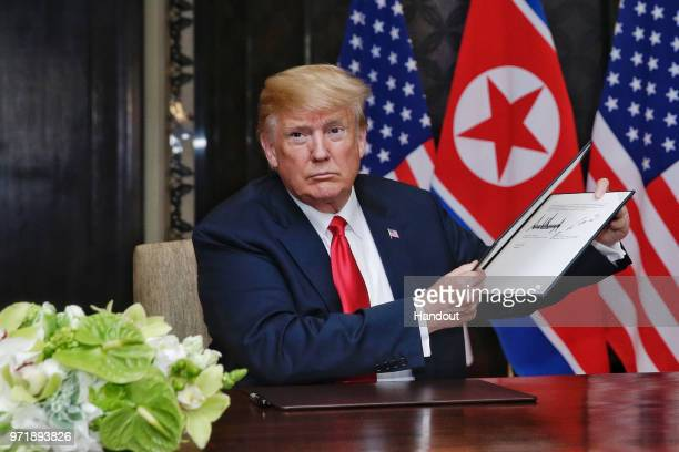 In this handout photograph provided by The Strait Times US President Donald Trump with North Korean leader Kim Jongun during their historic USDPRK...