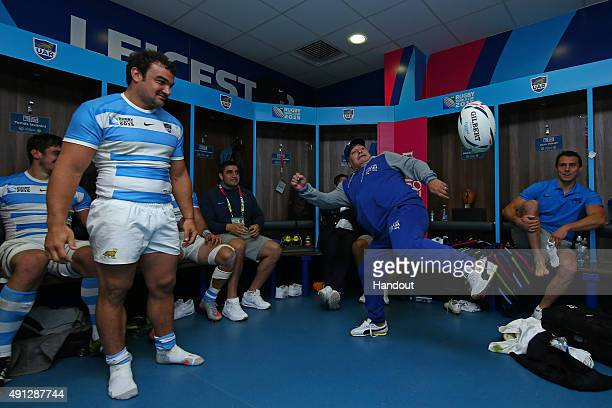 In this handout photograph provided by World Rugby Diego Maradona juggles a rugby ball watched by Agustin Creevy as he visits the Argentina dressing...