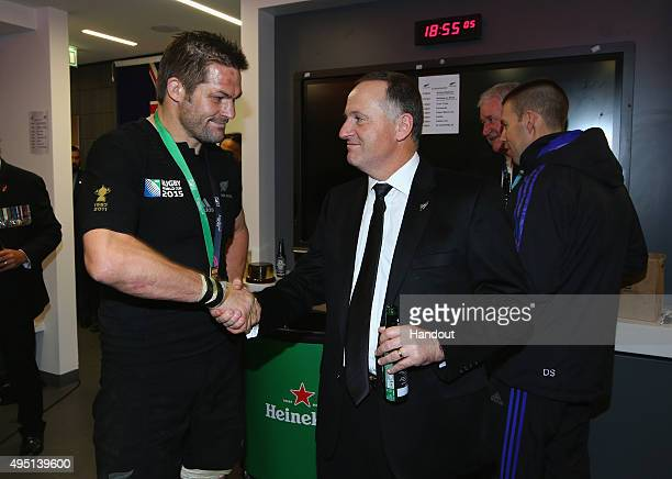 In this handout photograph provided by World Rugby Richie McCaw of the New Zealand All Blacks is congratulated by John New Zealand Prime Minster John...