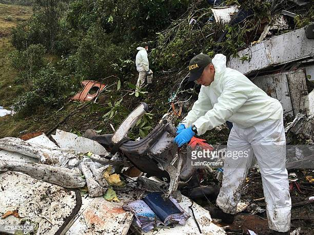 In this handout picture by Defensa Civil Antioquia Police officers work on the wreckage of the Lamia plane wich transported Brazilian football team...