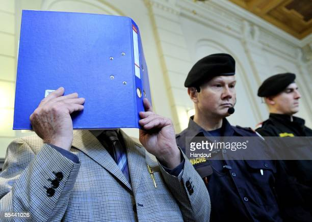 In this handout picture Josef Fritzl covers his face at the beginning of his trial at the country court of St Poelten on the beginning of his trial...
