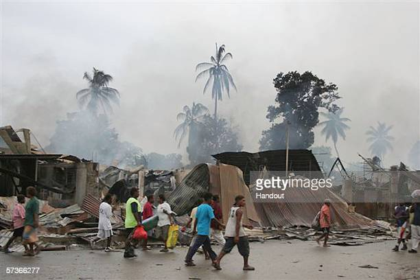 In this handout picture provided by PINA people walk past burned out buildings after rioting took place April 19, 2006 in Honiara, Solomon Islands....