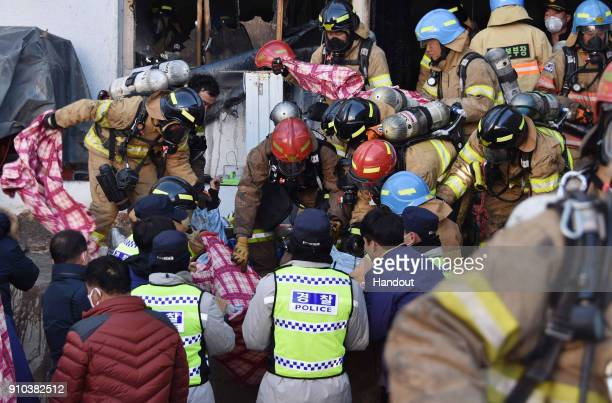 In this handout picture provided by the Kim Gu YeonGyeongnam Domin Ilbo Rescue workers remove bodies from a hospital fire on January 26 2018 in...