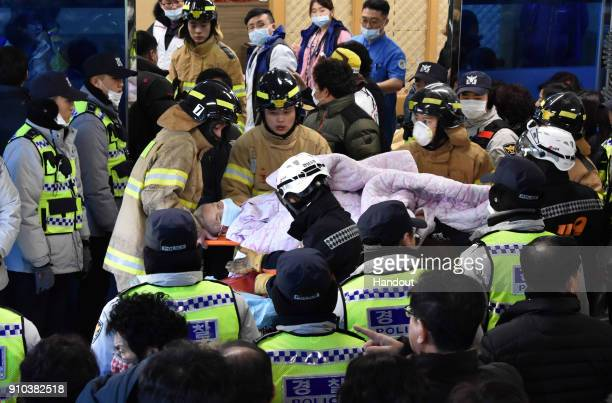 In this handout picture provided by the Kim Gu YeonGyeongnam Domin Ilbo Rescue workers remove a survivor from a hospital fire on January 26 2018 in...