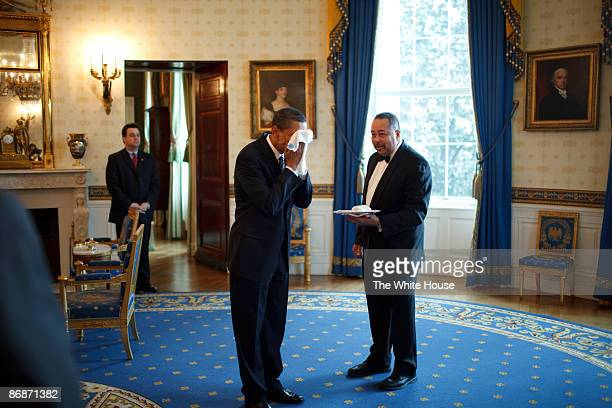 In this handout provide by the White House US President Barack Obama wipes his face with a cloth handed to him by White House Butler Von Everett in...