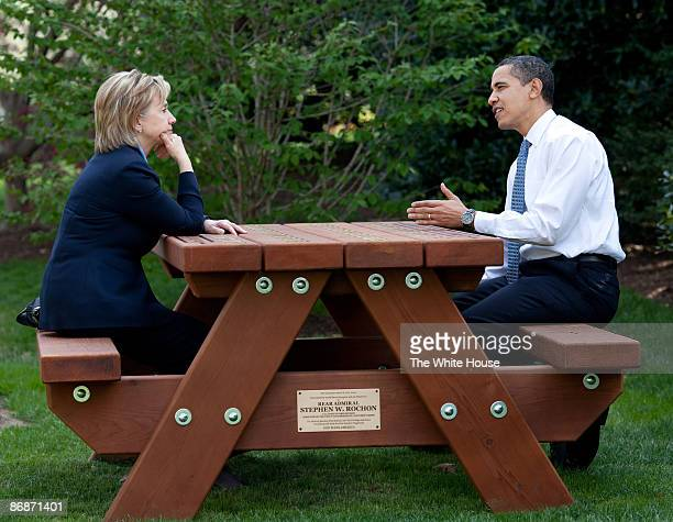 In this handout provide by the White House US President Barack Obama walks with Secretary of State Hillary Rodham Clinton speak together sitting at a...