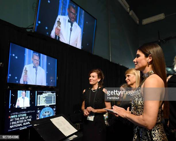 In this handout provided by AMPAS actor Sandra Bullock watches a video feed of writer writer Jordan Peele accept the Best Original Screenplay award...