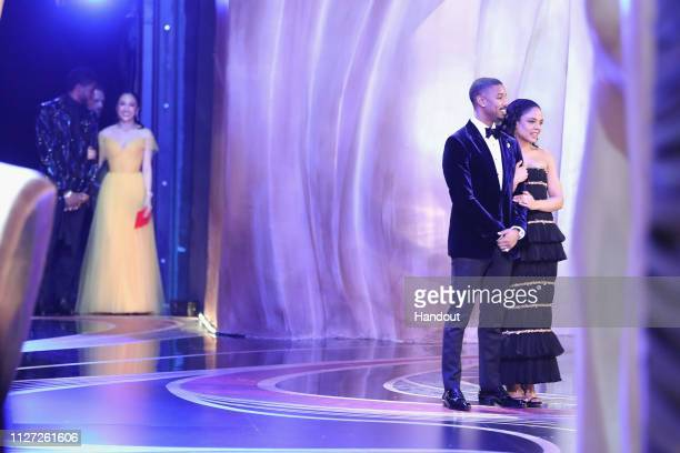 In this handout provided by AMPAS Chadwick Boseman and Constance Wu look on backstage as presenters Michael B Jordan and Tessa Thompson speak on...