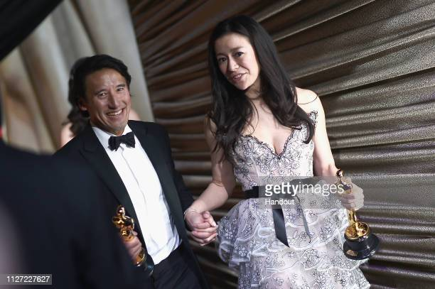 In this handout provided by AMPAS Free Solo filmmakers Jimmy Chin and Elizabeth Chai Vasarhelyi pose with the Best Documentary Feature award...