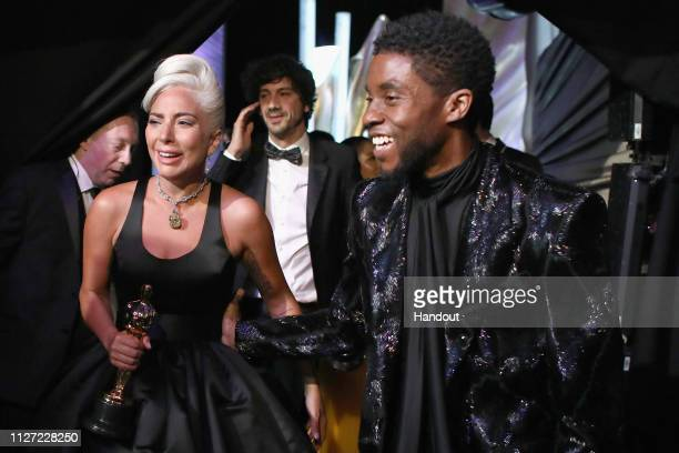 In this handout provided by AMPAS Lady Gaga poses with the Music award for 'Shallow' from 'A Star Is Born' backstage with presenter Chadwick Boseman...