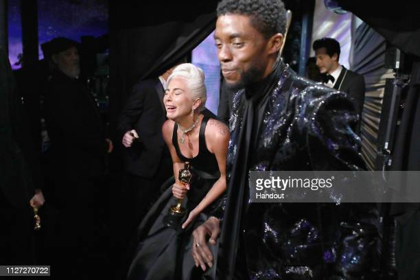 In this handout provided by AMPAS Lady Gaga poses with the Music award for 'Shallow' from 'A Star Is Born' with presenter Chadwick Boseman backstage...