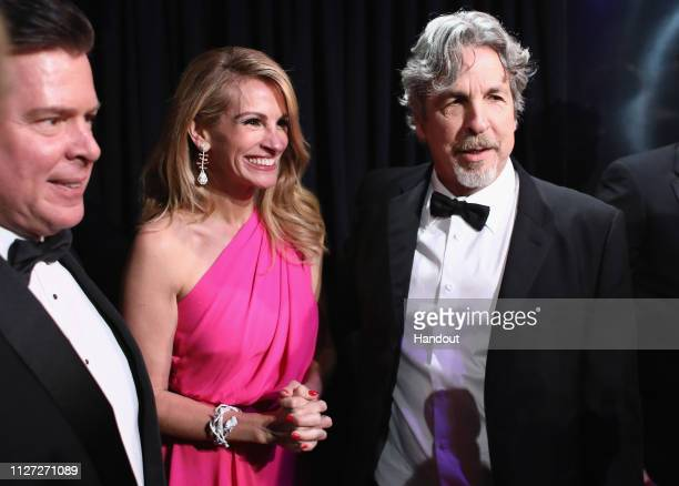In this handout provided by AMPAS Peter Farrelly poses with the Best Picture and Best Original Screenplay award for 'Green Book' with Julia Roberts...
